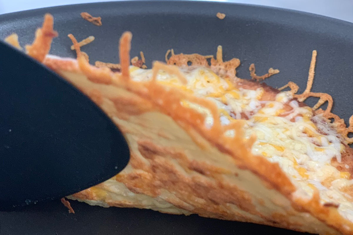 a ketodilla tortilla ready to be flipped in a pan
