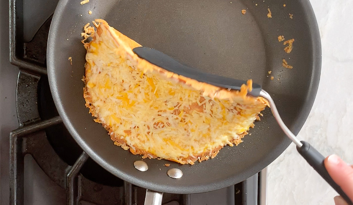a ketodilla tortilla loaded with cheese getting flipped in a pan with a spatula