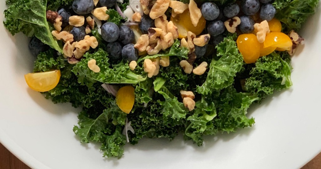 a large bowl of massaged kale salad with walnuts, blueberries and tomatoes on top
