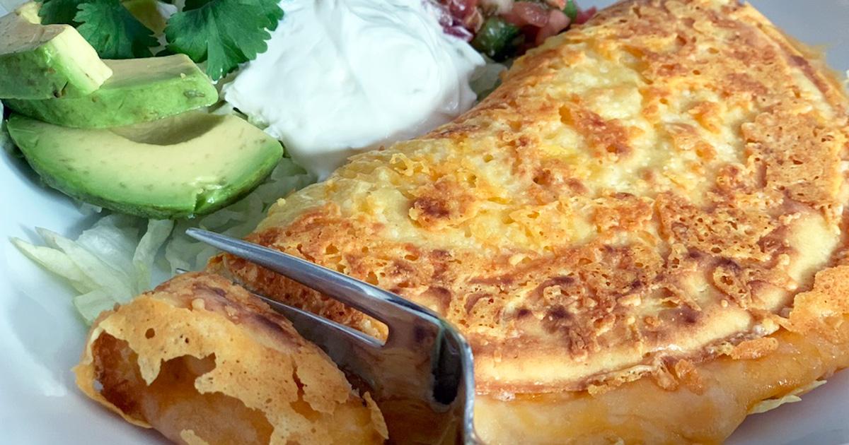 a fork cutting into a cheesy keto quesadilla