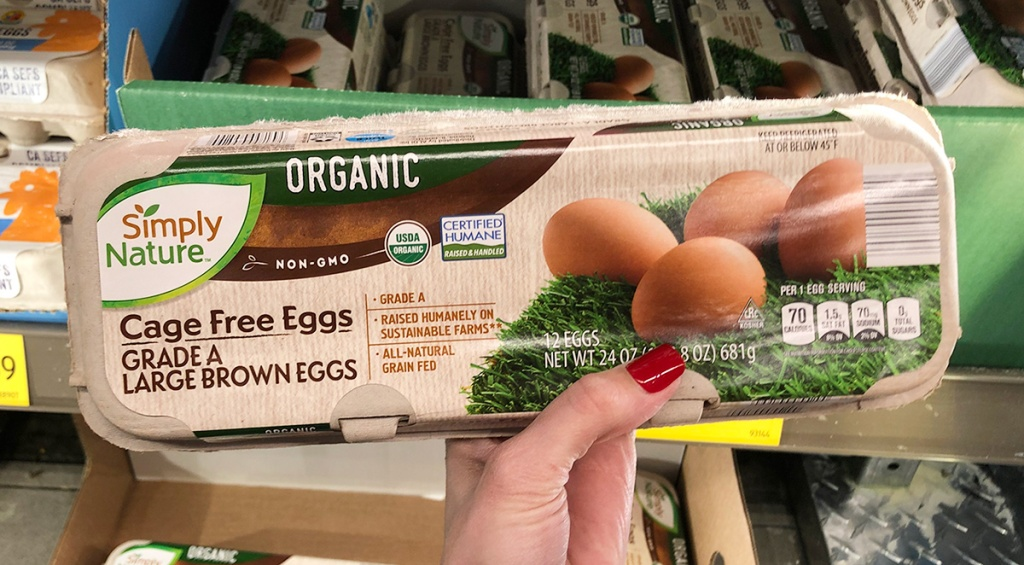 hand holding organic cage free brown eggs at aldi