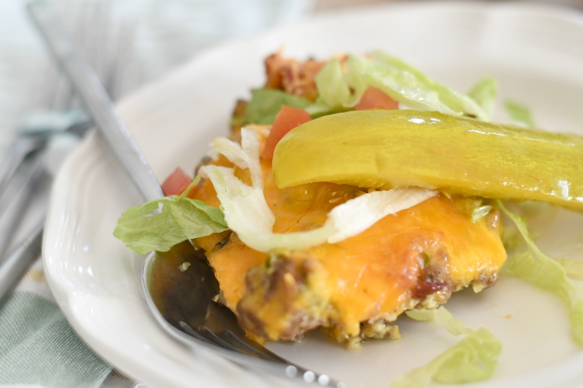 piece of keto cheeseburger casserole served with pickle and lettuce