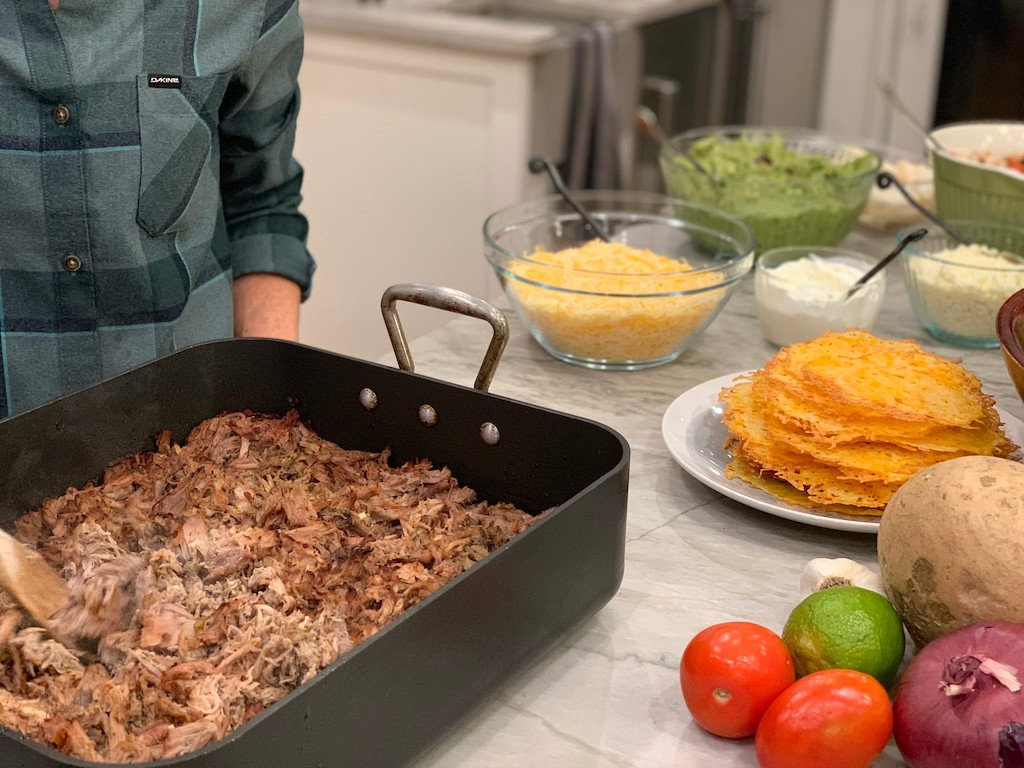 shredded pork in pan with toppings (shredded cheese, sour cream, vegetables and more)