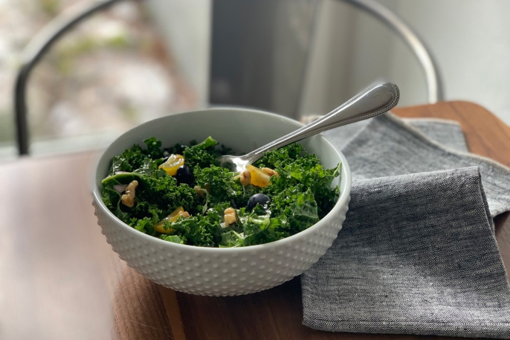 a white salad bowl with a helping of kale superfood salad
