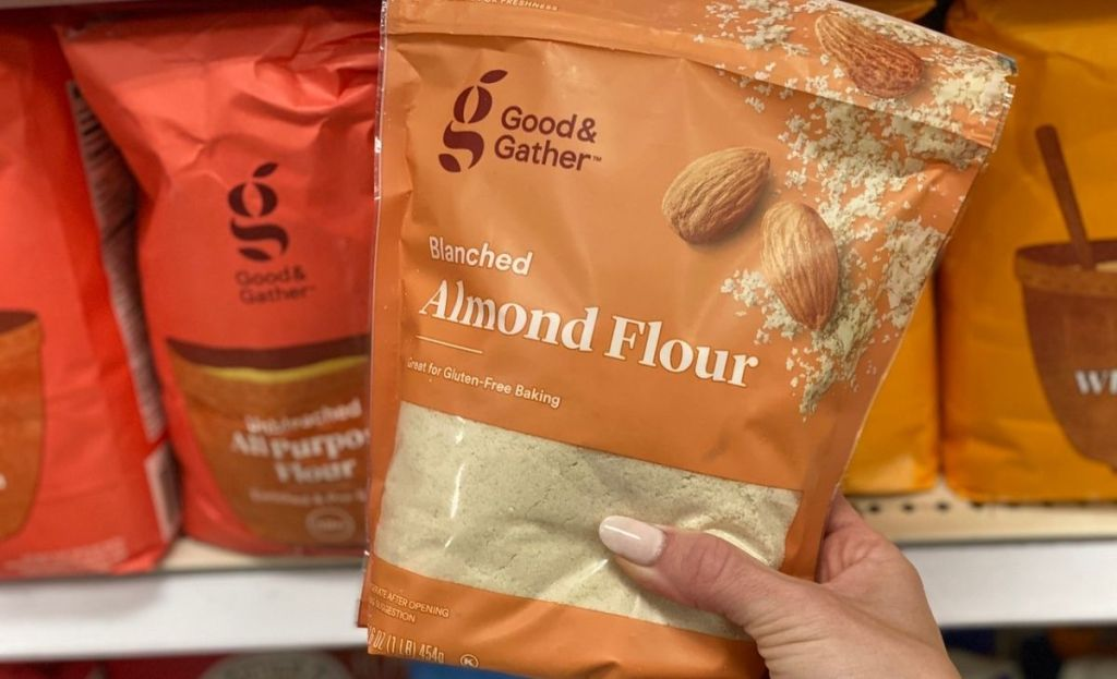 A hand holding a bag of almond flour at the store