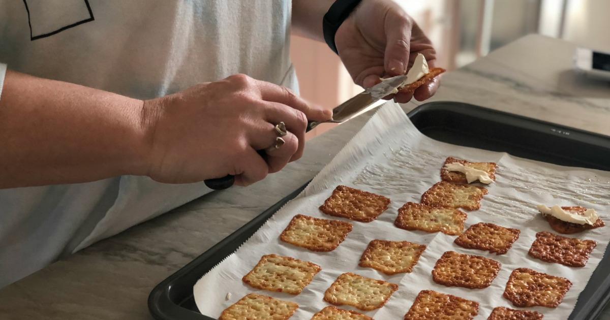 smearing cream cheese on keto cheese crisps