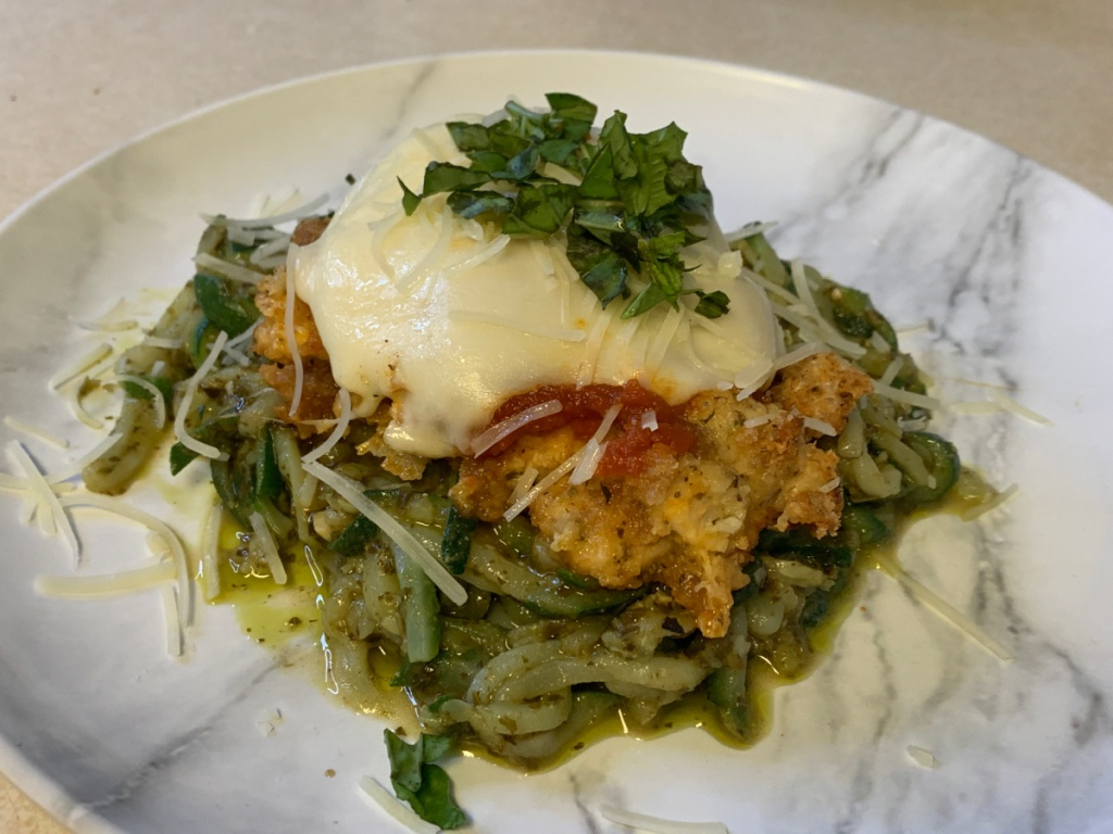 plated low-carb chicken parmesan over pesto noodles