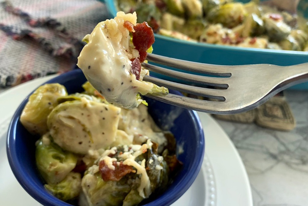 a fork with a roasted Brussels sprout, creamy Alfredo sauce, and bacon