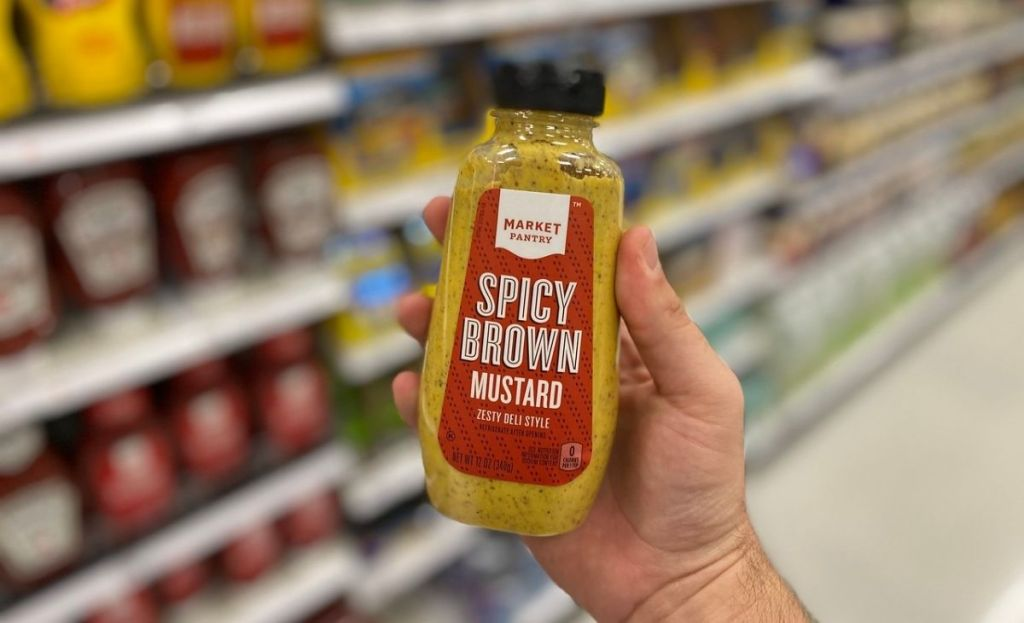 A hand holding some spicy brown mustard in a store