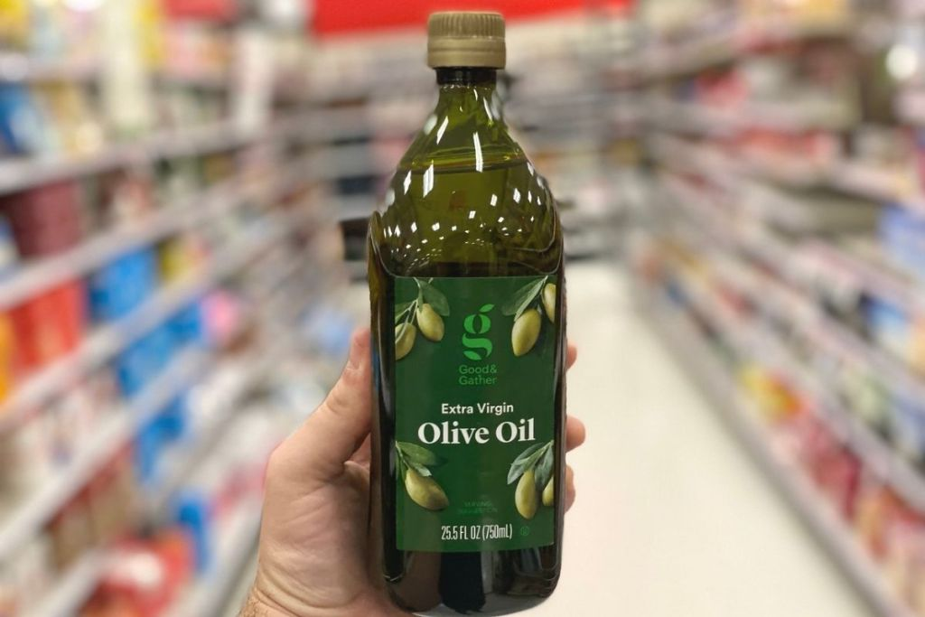 A hand holding a bottle of olive oil at a store
