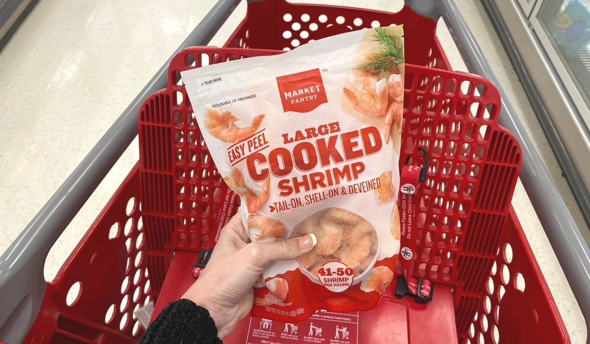 A hand placing a frozen bag of cooked shrimp in a Target shopping cart