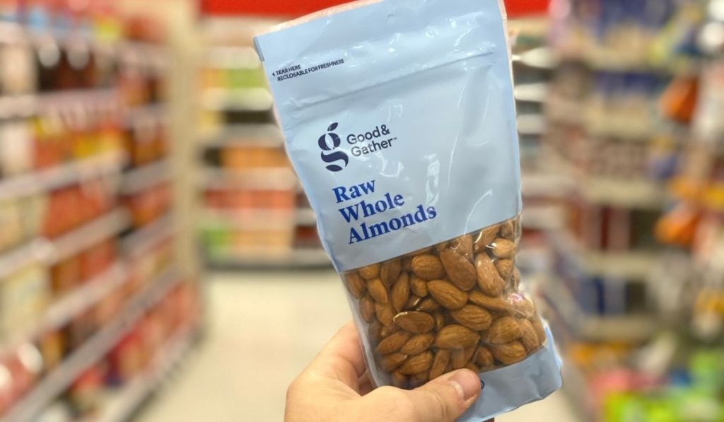 A hand holding a bag of raw almonds at a store