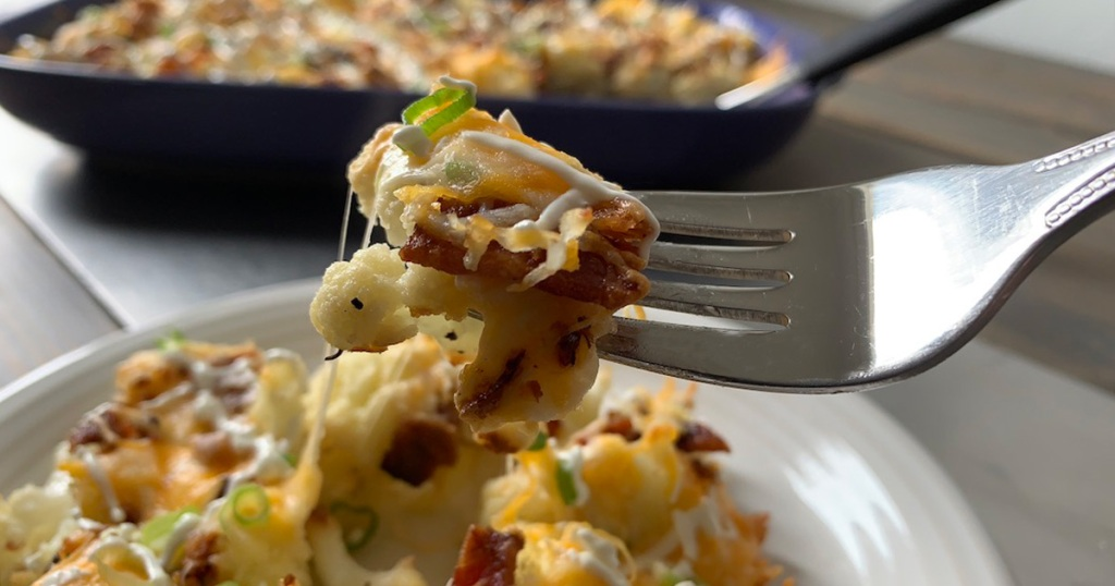 a heaping forkful of loaded cauliflower casserole with a big bite of bacon