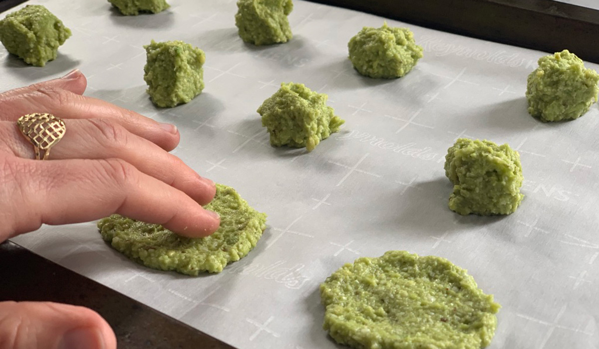 fingers pressing down avocado cheese batter into circles