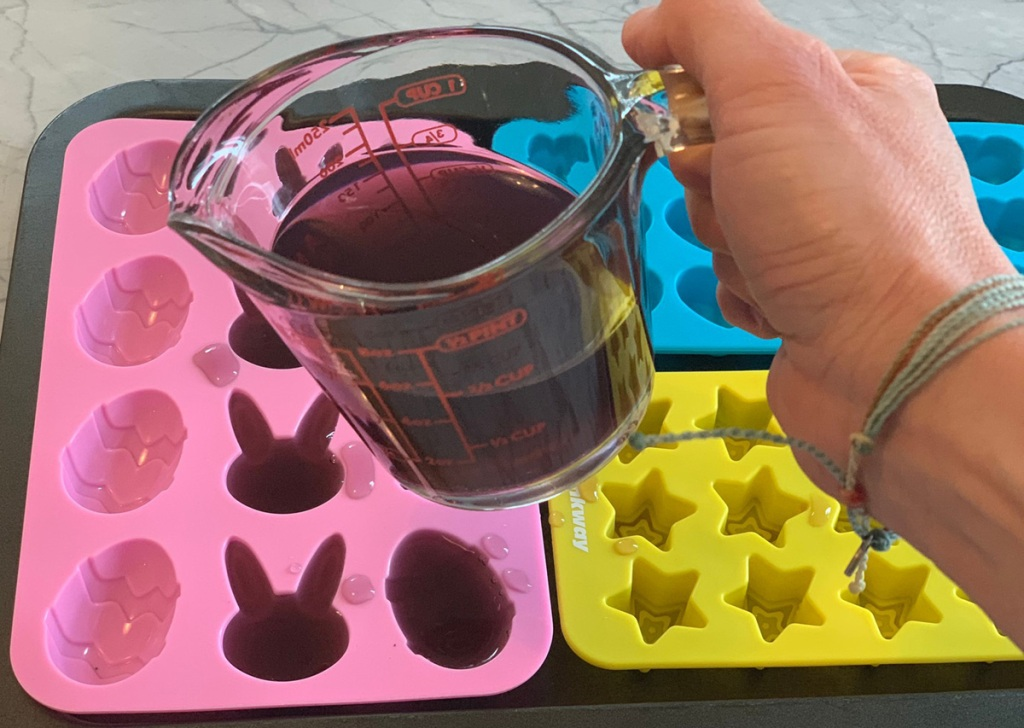 hand pouring jello mixture into molds