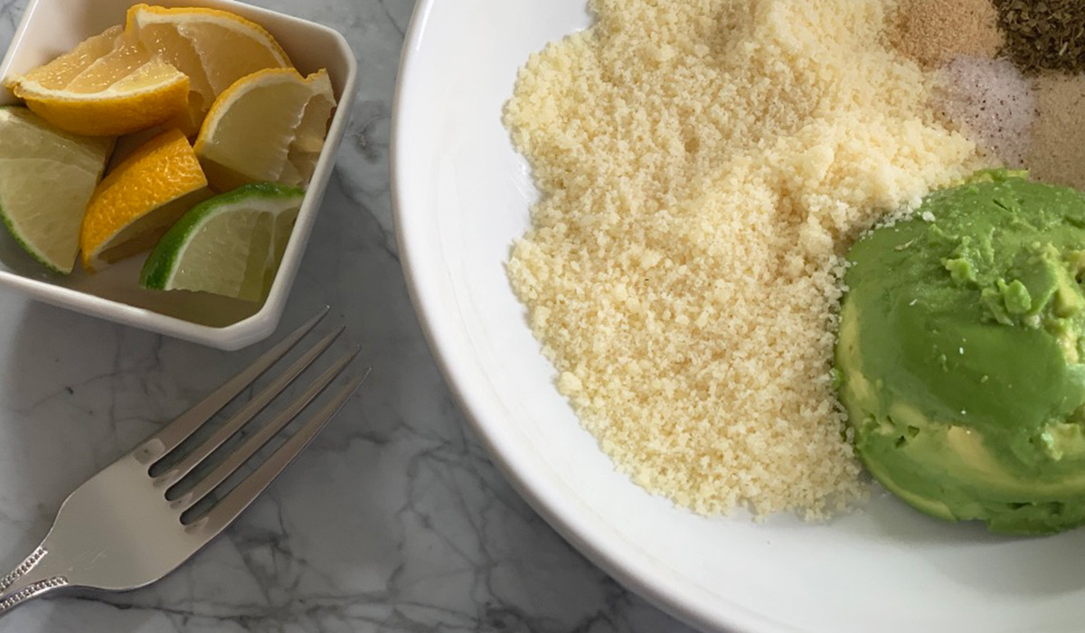 a bowl with parmesan cheese and avocado ready to be mashed