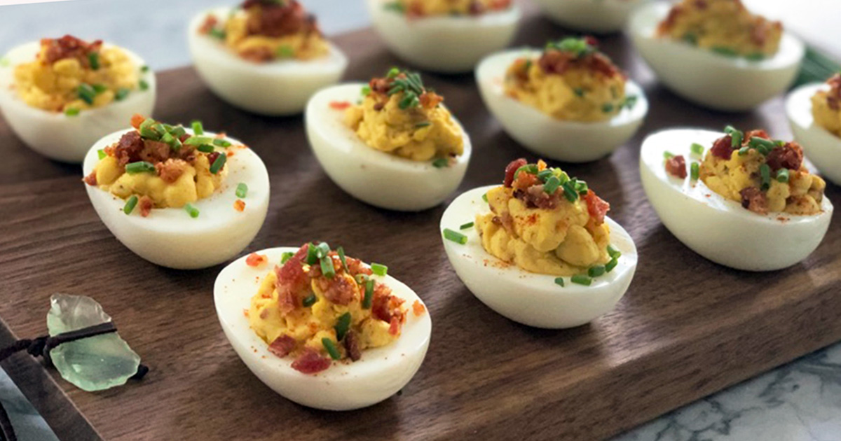 a wooden serving tray with keto bacon deviled eggs garnished with fresh chives