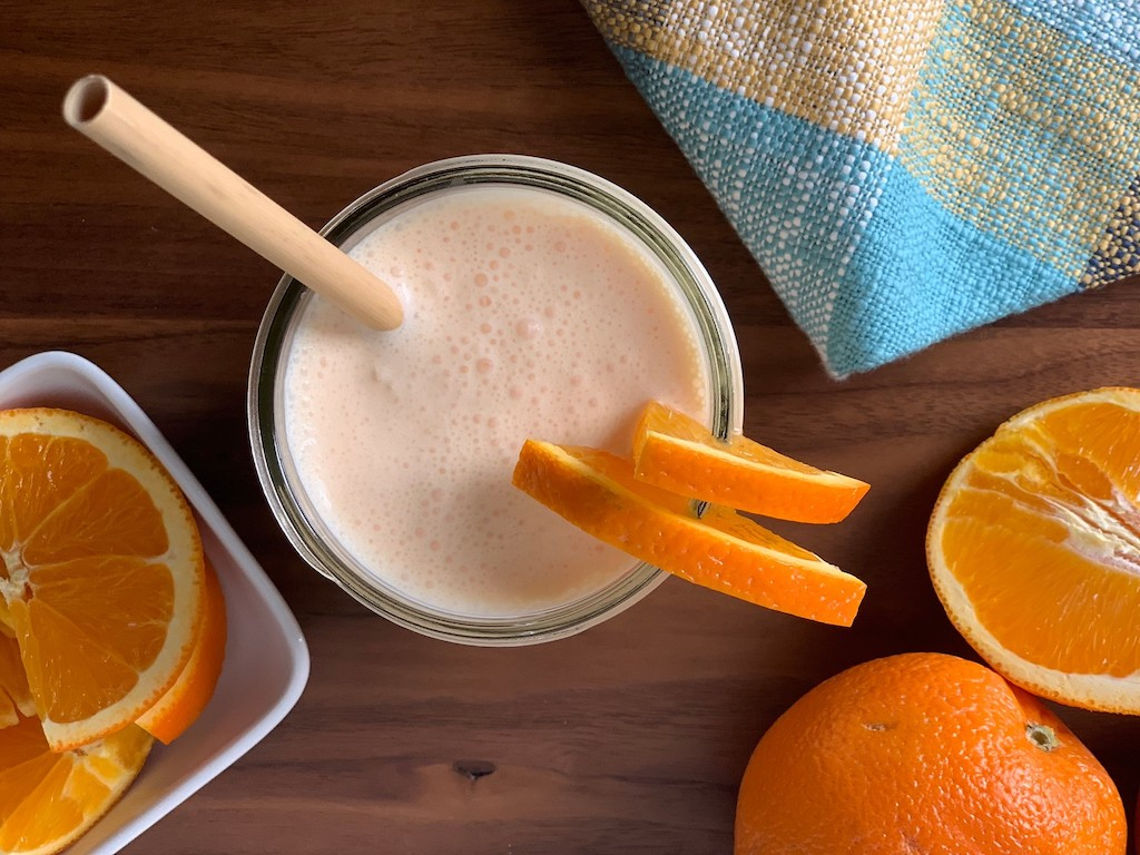 keto orange julius in mason jar with fresh oranges