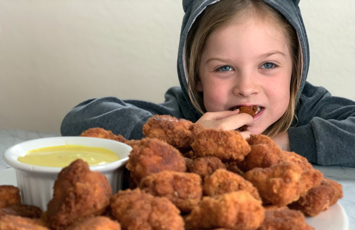 young girl eating a tasty southern fried chicken bite