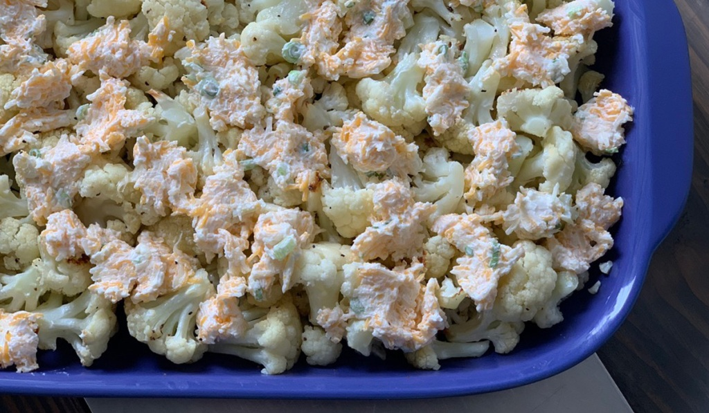 a baking dish with roasted cauliflower and spoonfuls of a cheesy, creamy mixture