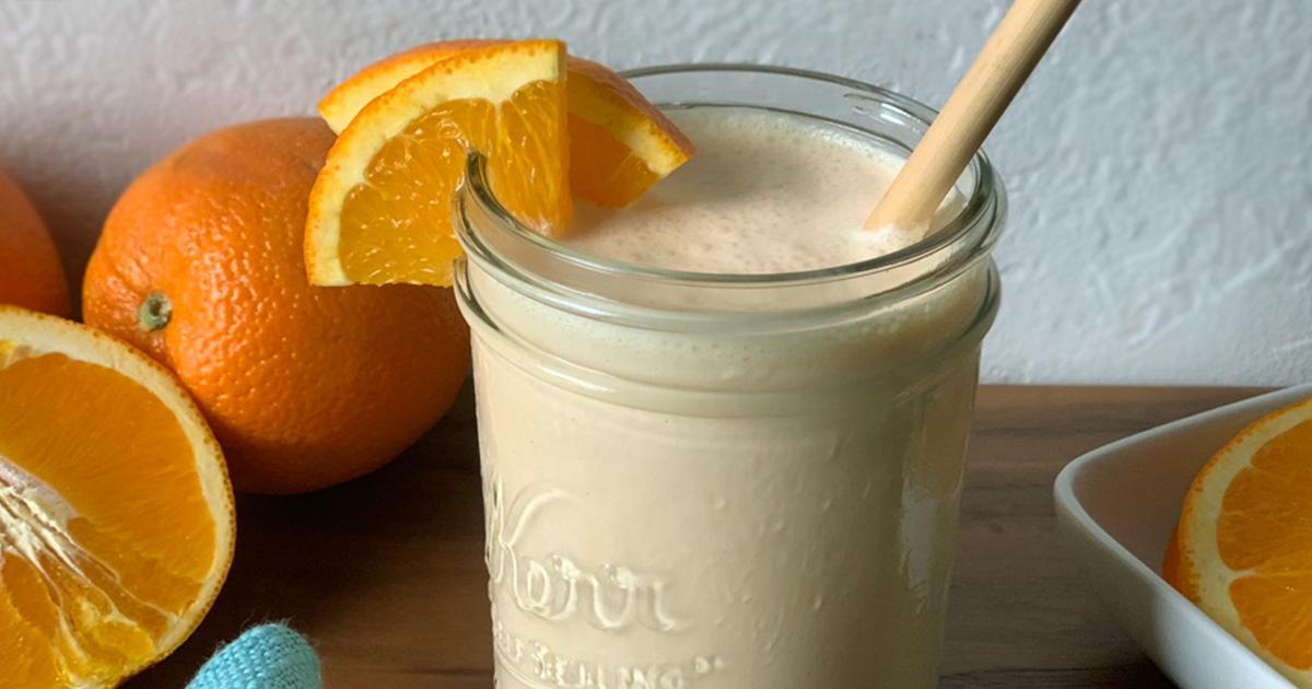 An Orange Julius served in a mason jar with orange wedges