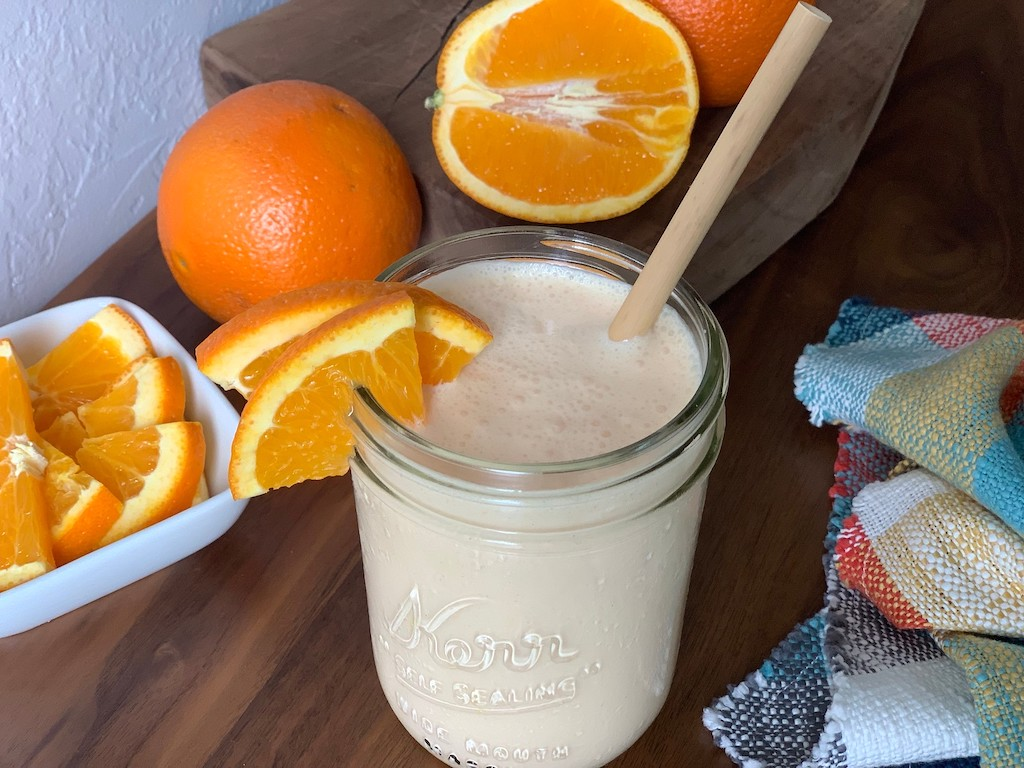 orange julius copycat drink in mason jar with fresh oranges