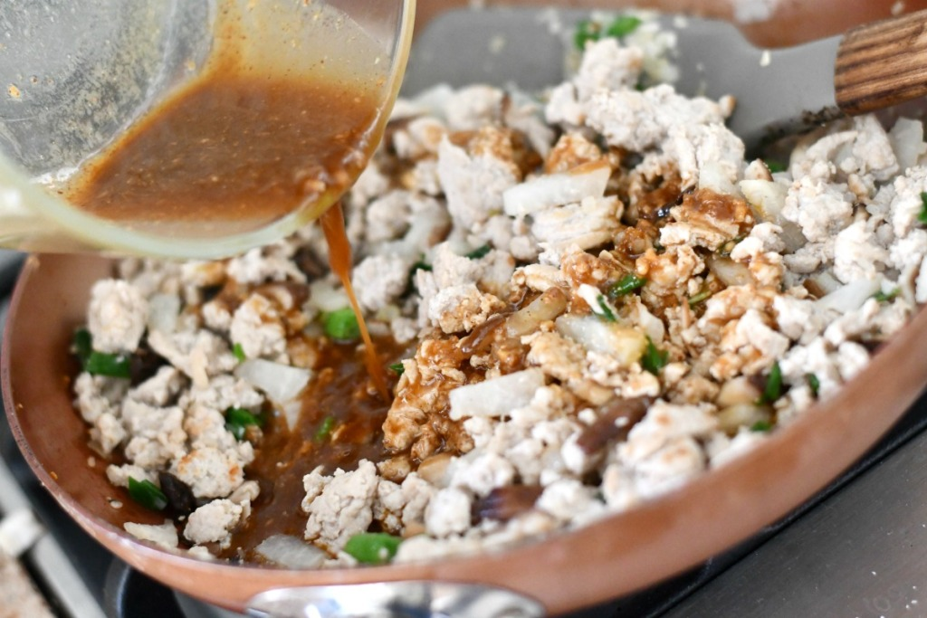 pouring sauce on keto lettuce wraps