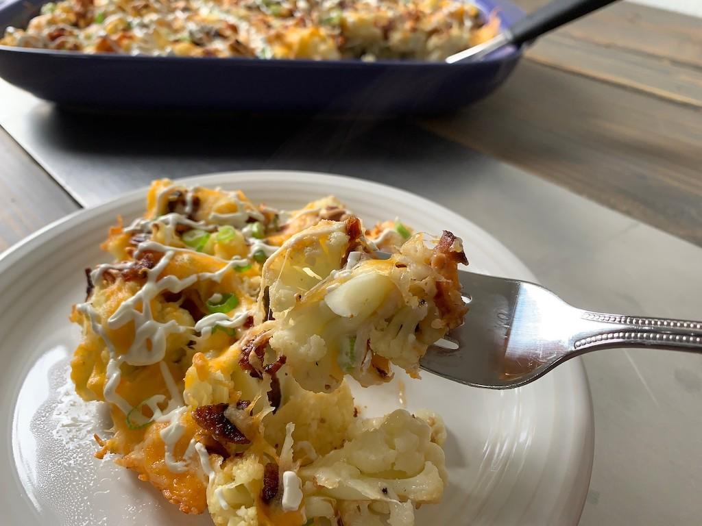 taking bite of keto loaded cauliflower casserole
