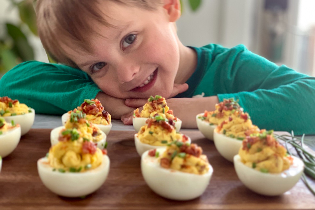 a young boy smiling over a tray of deviled eggs