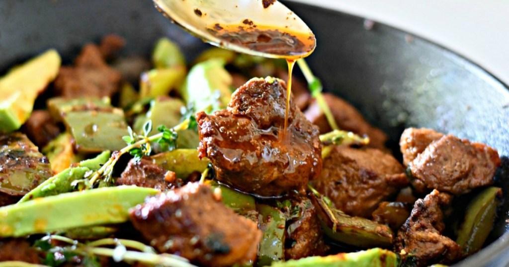 drizzling garlic butter over steak bites