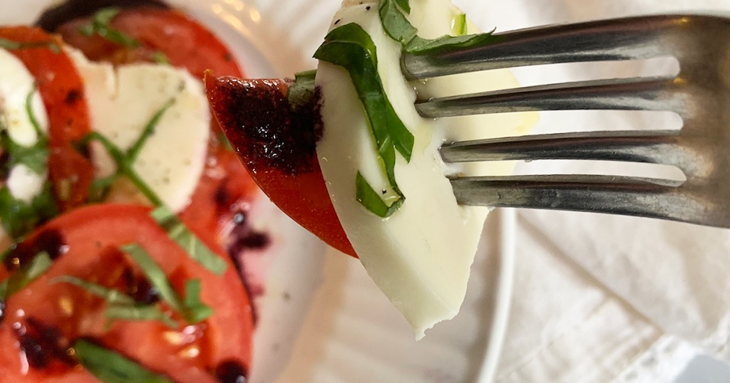 a forkful of Caprese salad with blackberry balsamic glaze