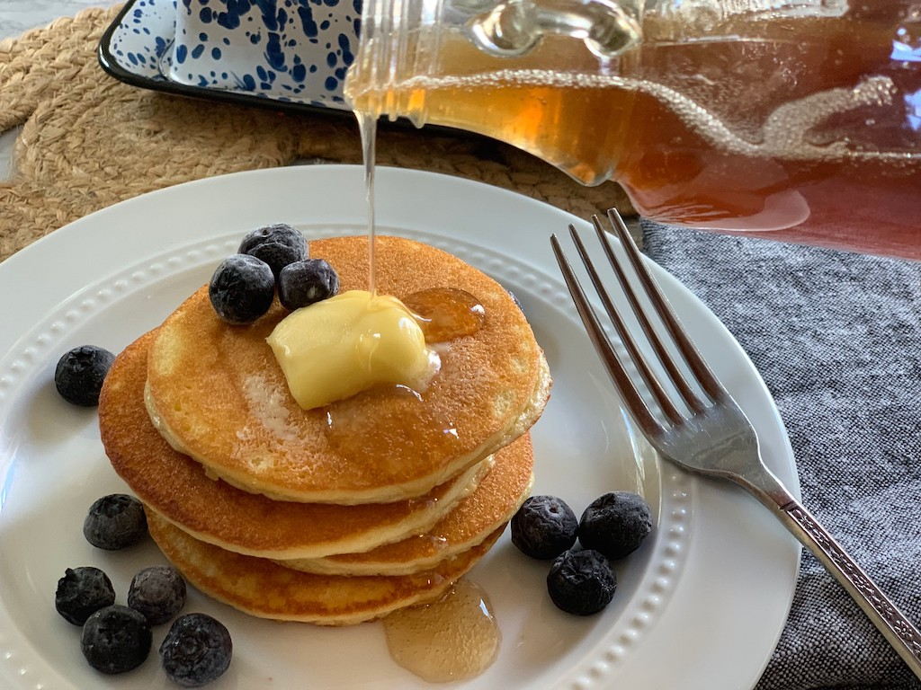 Keto pancakes with sugar free syrup being poured on them