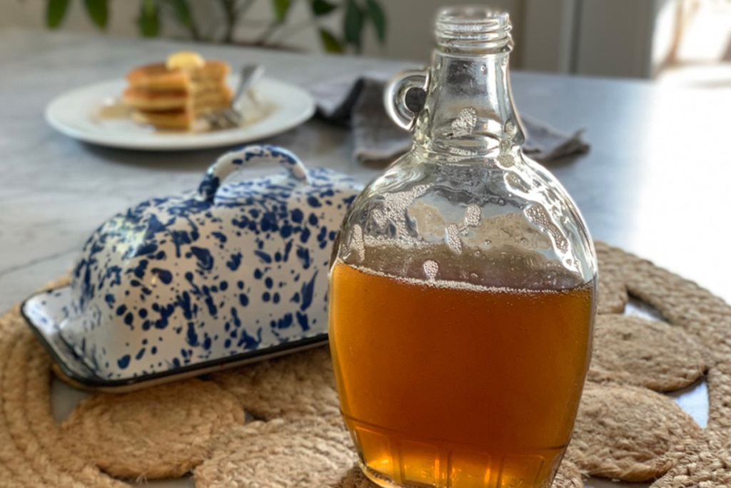 a glass bottle of keto pancake syrup on a table with a butter dish