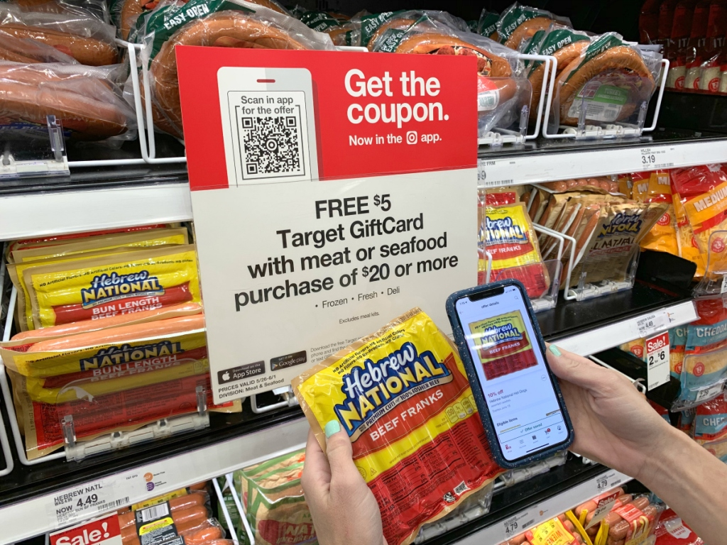 person holding package of Hebrew National hot dogs and phone at Target