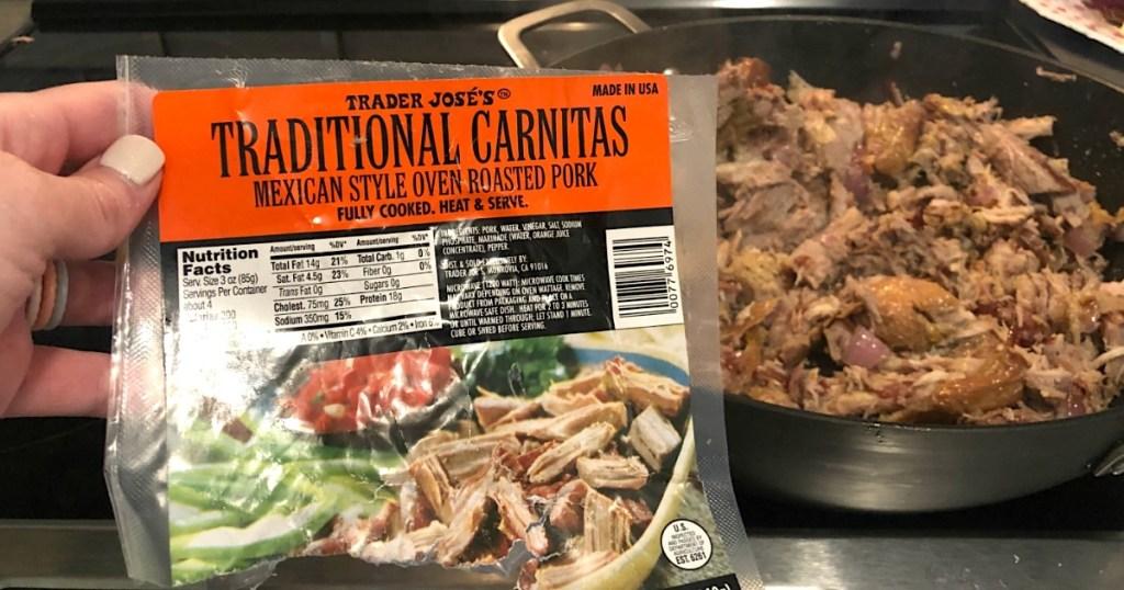 holding Trader Joe's Pork Carnitas bag with pork in pan