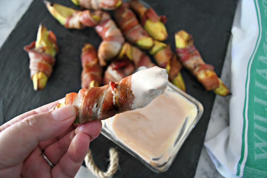 dipping a keto bacon wrapped avocado into mayo dipping sauce
