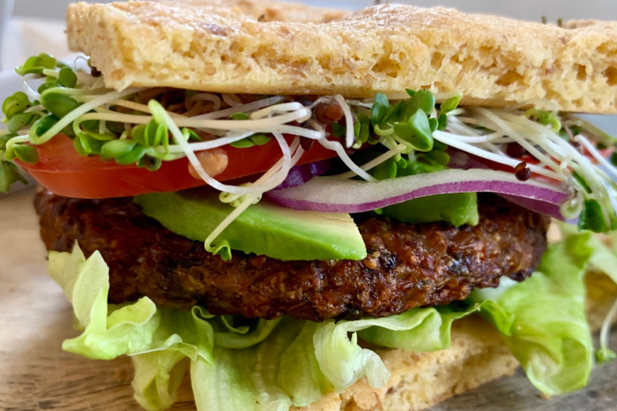 a low-carb veggie burger topped with sprouts, tomatoes, and red onions
