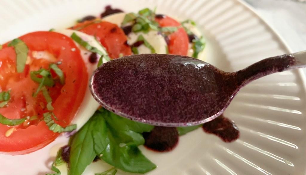 spoonful of blackberry balsamic glaze over caprese