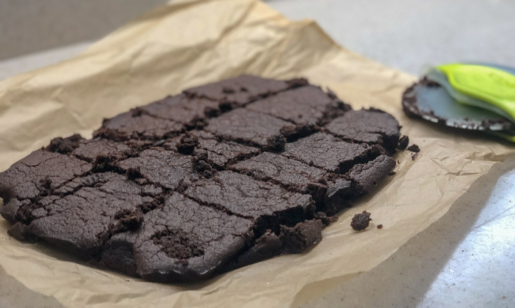 fudgy keto brownies — keto brownies on parchment paper cooling out of the oven