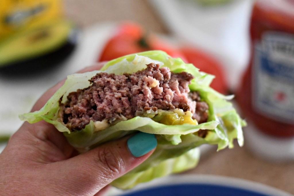 taking bites of a burger cabbage wrap
