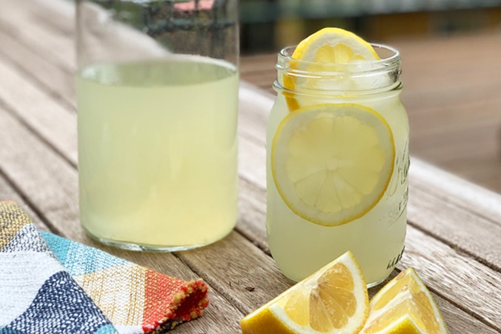 a pitcher of keto lemonade next to a glass of iced lemonade