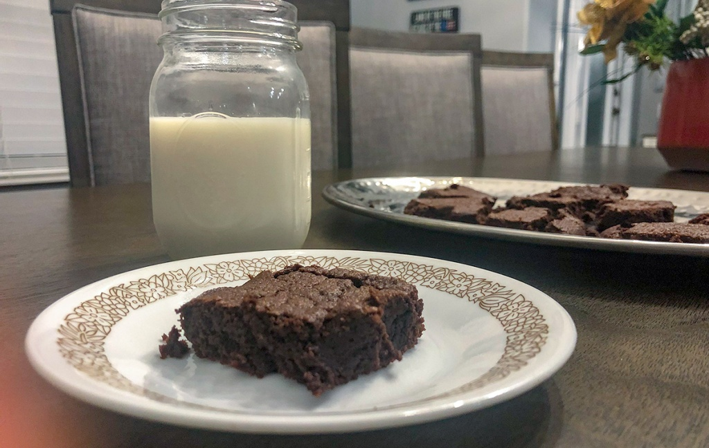 fudgy keto brownies — keto brownie on plate with glass of almond milk