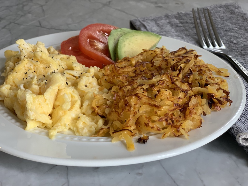 a lovely plate of breakfast that includes scrambled eggs and keto rutabaga hash browns