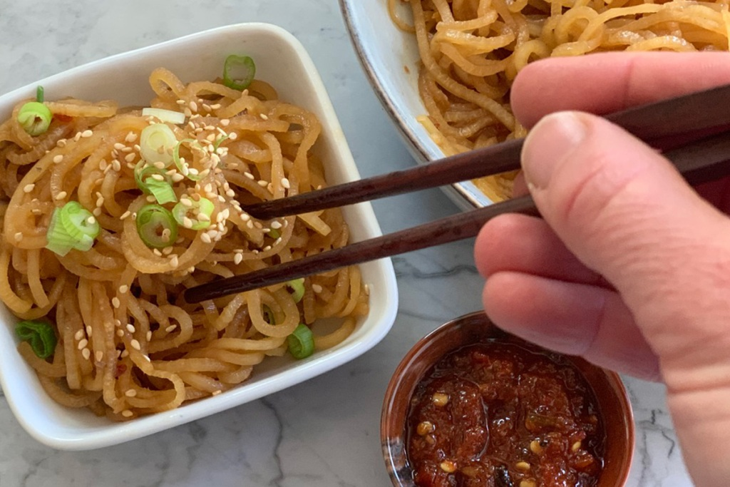chopsticks picking up low-carb sesame noodles