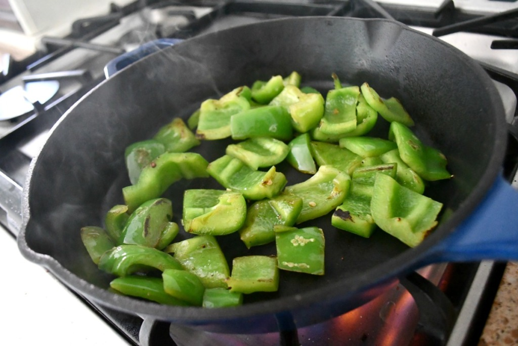 sauteed bell peppers in a cast iron skillet