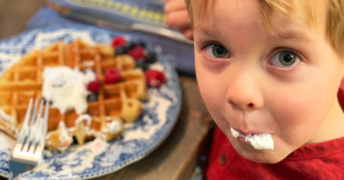 little boy eating keto waffles with whipped cream