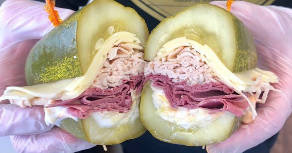 holding a pickle sandwich with turkey and cheese