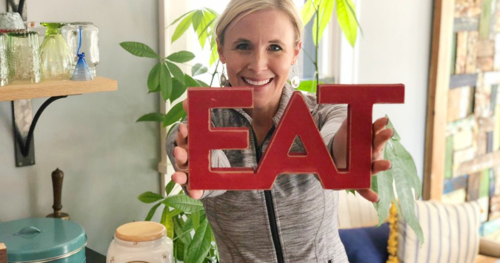 "woman holding up sign that says ""eat"""