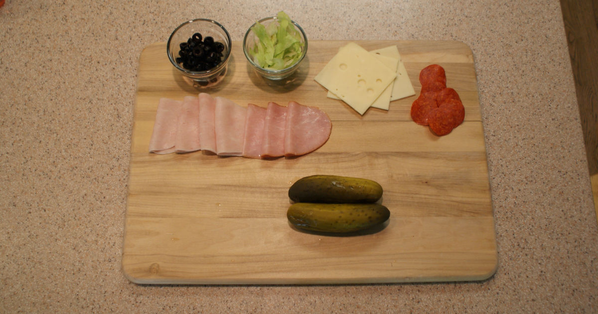 ingredients for a pickle sandwich on a cutting board