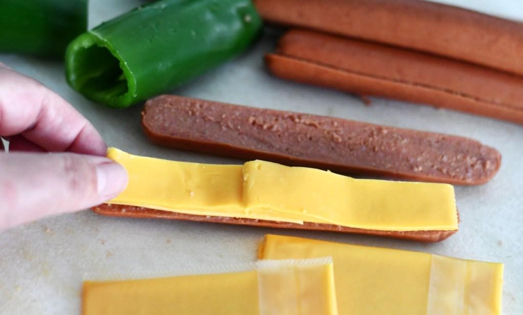 adding cheese to jalapeno hot dog